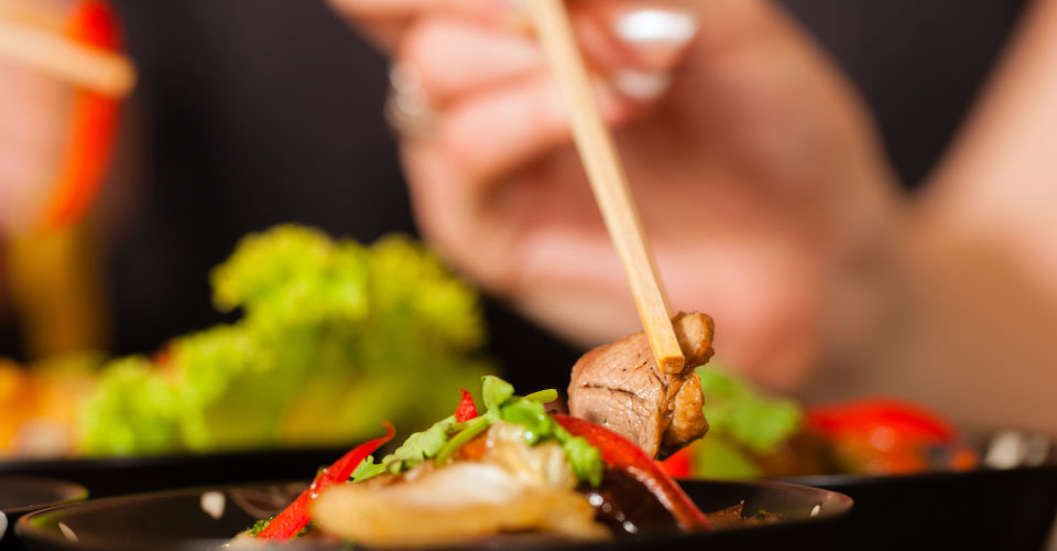 eating with chopsticks, close-up on hands and food